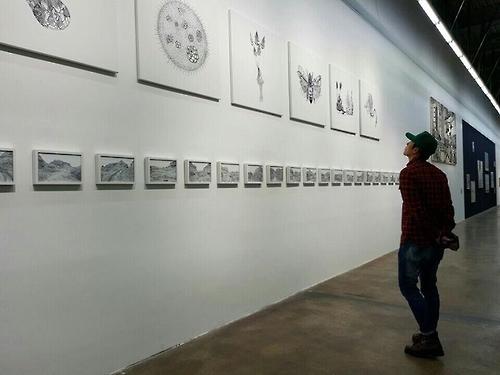 演员玄彬正在观看展览(韩联社/光州双年展组委会提供)