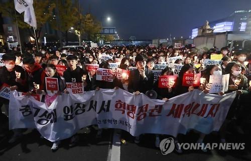 5日晚,聚集在市区的民众手持烛光向前行进,要求总统朴槿惠下台。(韩联社)