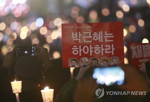 """参加集会的人群手持""""朴槿惠下台""""的标语。(韩联社)"""