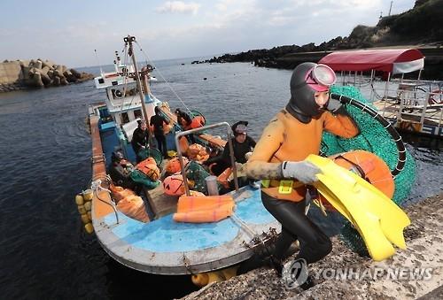 资料图片:济州西归浦海女们完成一天的作业后回岸,图片摄于2016年11月。(韩联社)