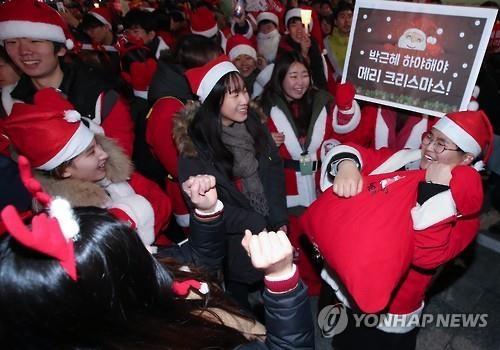 """12月24日,韩国民众集会,举出""""只有朴槿惠下台,才能圣诞快乐""""的标语。(韩联社)"""