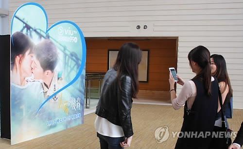 资料图片:2016年4月,香港粉丝在韩剧《太阳的后裔》香港宣传活动上拍照。(韩联社)