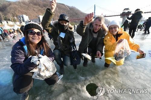 资料图片:外国游客在2016年华川山鳟鱼庆典上体验冰钓。(韩联社)