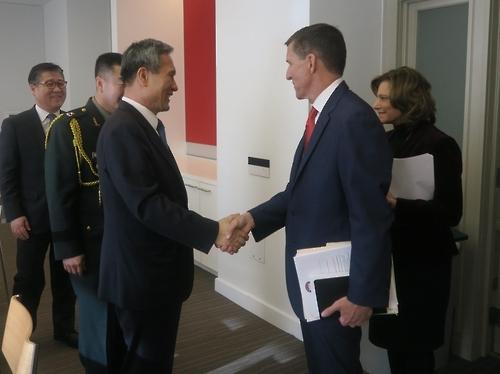 资料图片:当地时间2017年1月9日,在华盛顿,韩国国家安保室长金宽镇(左三)和美国下届政府国家安全助理提名人迈克尔·弗林(右二)在会谈前握手。(韩联社)