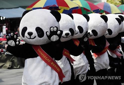 """资料图片:2015年4月,一群""""熊猫""""出现在首尔南大门市场。这是韩国新世界集团举办的开发南大门市场及吸引中国游客的活动。(韩联社)"""