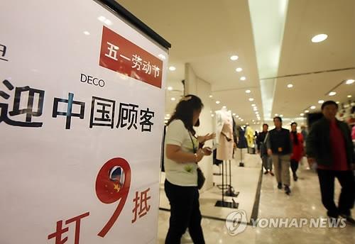 资料图片:2015年4月,位于首尔小公洞的乐天百货打出欢迎中国顾客并为中国游客提供打折优惠的告示牌。(韩联社)
