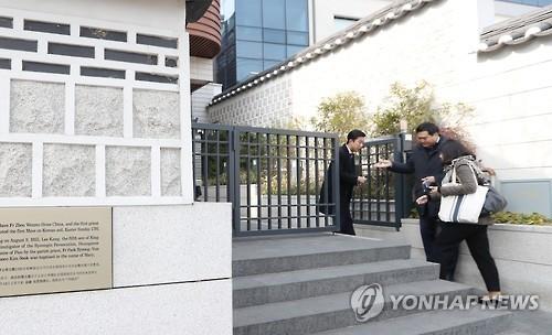1月19日上午,在首尔市嘉会洞天主教堂,参加Rain和金泰希婚礼的一位宾客走进教堂。(韩联社)