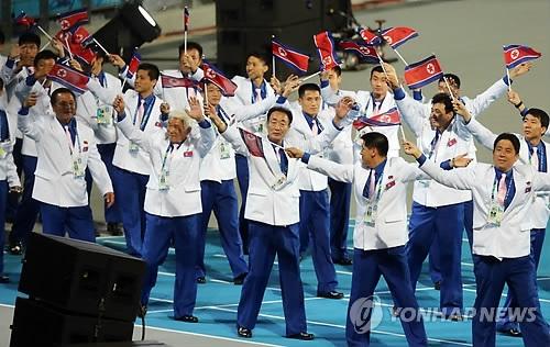 资料图片:2014年10月4日,在仁川亚运会闭幕式上,朝鲜代表队挥舞着朝鲜国旗入场。(韩联社)