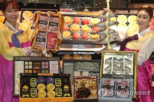 资料图片:1月9日,在乐天玛特清凉里店,促销员推介春节礼品。(韩联社)