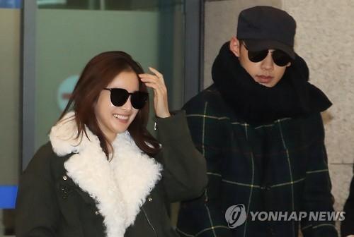 1月27日,度完蜜月的金泰希和Rain乘机回国。(韩联社)