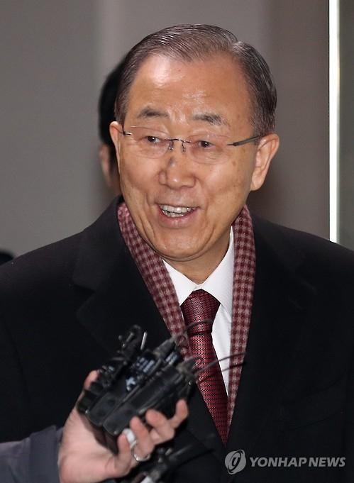 2月2日,在首尔舍堂洞,潘基文走出自宅时面带笑容向在家前等候的媒体记者们问候。(韩联社)