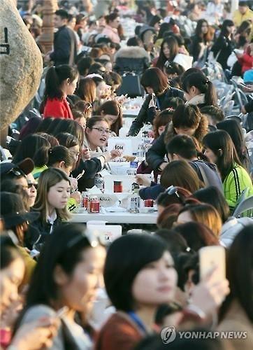 资料图片:2016年3月28日下午,在仁川市月尾岛文化街,几千名傲澜员工一起吃炸鸡喝啤酒。(韩联社)