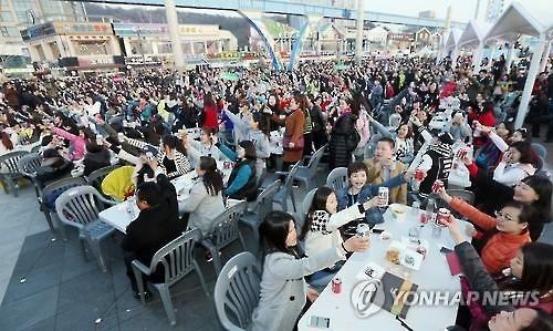 资料图片:2016年3月28日下午,在仁川市月尾岛文化街,几千人举杯共饮。(韩联社)