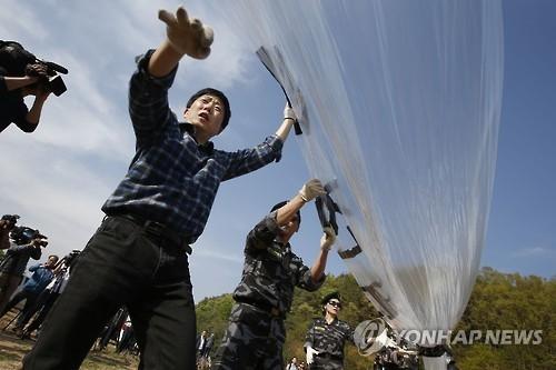 资料图片:自由北韩运动联合会负责人朴相学(左一)在韩朝边境准备释放气球向朝投送传单。