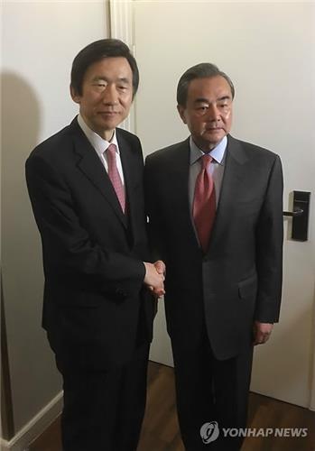当地时间2月18日,在德国慕尼黑万豪酒店,韩国外长尹炳世(左)与中国外交部长王毅在会谈前合影留念。(韩联社)