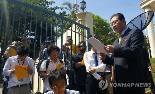 2月20日,朝鲜驻马来西亚大使姜哲(右)在使馆前召开记者会,称无法信任马方调查。(韩联社)