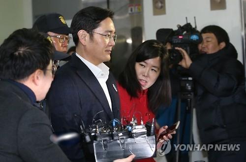 资料图片:抵达亲信门独检组办案地的李在镕(左二)被记者包围。(韩联社)
