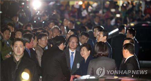 朴槿惠乘车抵达私邸后下车,同等候的青瓦台前核心幕僚和挺朴派国会议员握手。(韩联社)