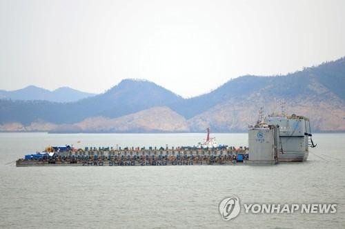 3月22日上午,在全罗南道珍岛郡东巨次岛海域,上海打捞局的2艘驳船准备抬起沉船。(韩联社)