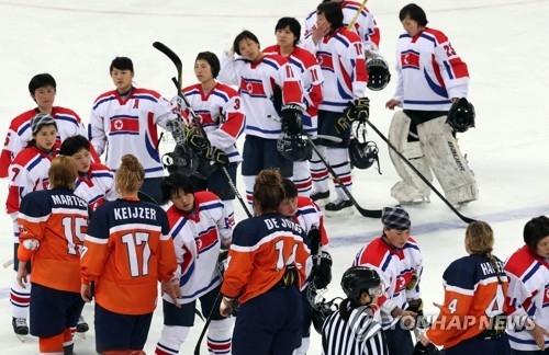资料图片:4月3日下午,在韩国江陵,朝鲜女子冰球队与荷兰队赛后握手。(韩联社)