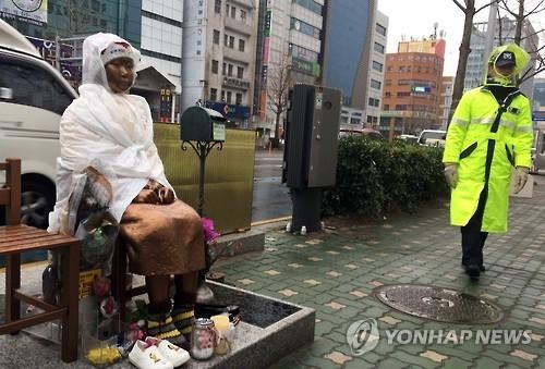 资料图片:2月20日上午,在釜山日领馆前,一名韩国警察走过慰安妇少女铜像旁。(韩联社)