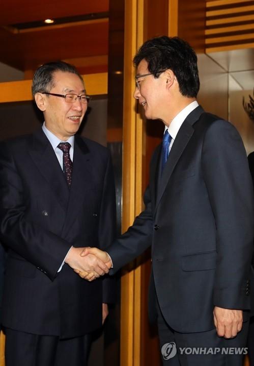 刘承旼(右)和武大伟亲切握手。(韩联社)