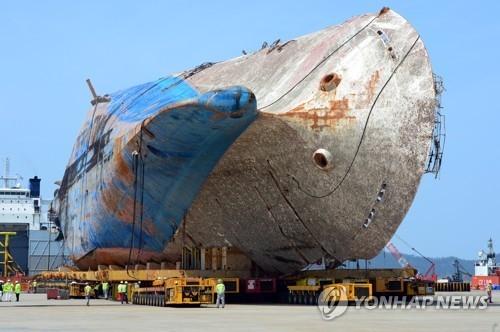"""4月11日下午,在木浦新港,工作人员正将模块运输车抽离""""世越""""号船体。(韩联社)"""
