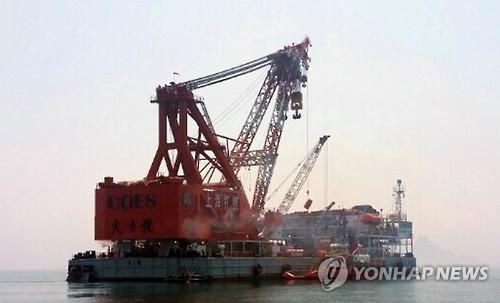 """资料图片:2015年8月15日,中国交通运输部上海打捞局企业联合体的""""大力""""号打捞工程船在""""华和""""轮的拖带下抵达""""世越""""号打捞现场。(韩联社)"""