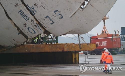 4月17日上午,在全罗南道木浦新港,工作人员(橘色)准备登船进行作业。(韩联社)