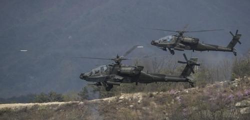 """4月26日,在京畿道升进训练场,美军""""阿帕奇""""直升机发射火箭弹。(韩联社)"""
