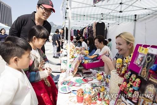 资料图片:去年9月25日,在首尔光化门广场,孩子们在外国人跳蚤市场挑选物品。(韩联社)