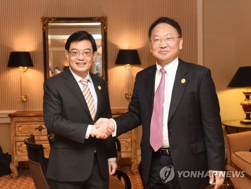 5月5日,在日本横滨,韩国财长柳一镐(右)和新加坡财长王瑞杰会前握手。(韩联社)