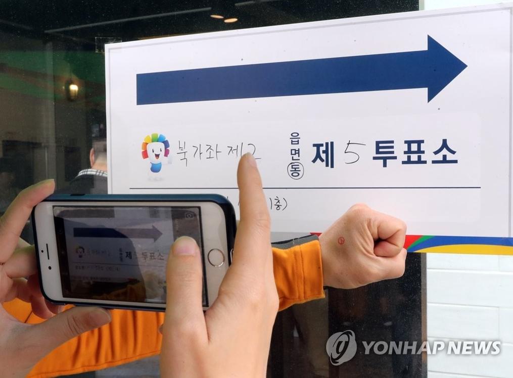 5月9日上午,在首尔西大门区一投票站内,选民投完票后拍照留念。(韩联社)