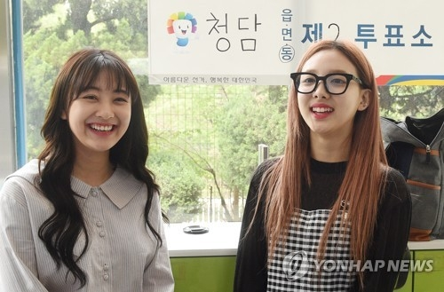 人气女团TWICE成员娜琏(右)、志效参加大选投票。(韩联社)