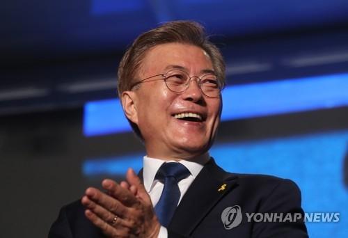 5月9日晚,在首尔光化门广场,开票工作结束前已确定当选的文在寅笑容满面。(韩联社)