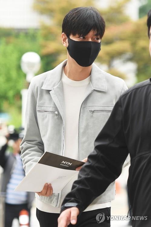 图为李敏镐身穿灰色夹克,戴着口罩现身区政府大楼。(韩联社)