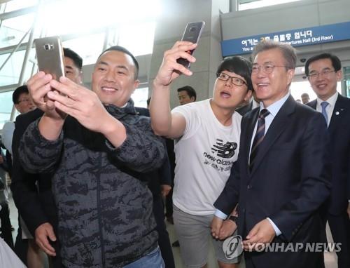 """5月12日上午,在仁川机场,文在寅在出席""""总统上门活动""""前与出境旅客亲切合影。(韩联社)"""