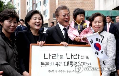 5月10日上午,文在寅(左三)和金正淑(左二)接过邻居联名庆祝入主青瓦台的匾额后喜笑颜开。(韩联社)