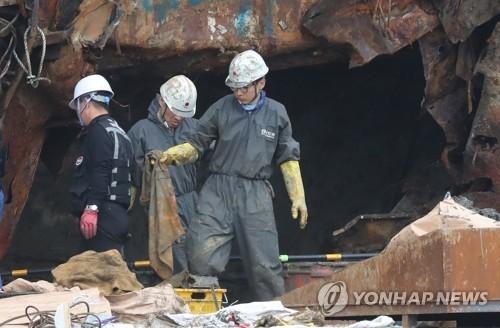 """5月12日,""""世越""""号现场处理本部工作人员在船尾发现疑似失踪者遗骨。(韩联社)"""