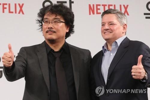 5月15日,韩国导演奉俊昊(左)和Netflix首席内容官泰德·萨兰多斯在《玉子》记者会上摆姿势供媒体拍照。(韩联社)