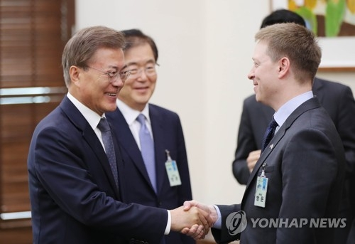 韩国总统文在寅(左一)与到访的美国白宫亚洲事务资深主管马修·波廷杰亲切握手。(韩联社/青瓦台提供)