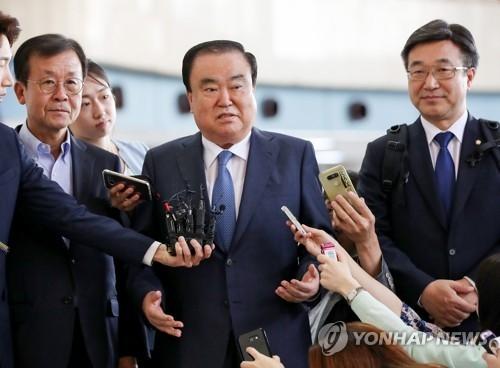5月17日,在金浦机场,韩国总统文在寅派往日本的特使、前国会副议长文喜相(中)启程赴日前接受记者采访。(韩联社)