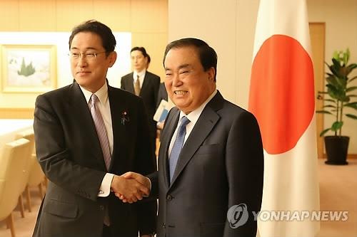5月17日,在东京,韩国总统特使文喜相(右)与日本外务大臣岸田文雄握手。(韩联社)