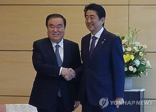 5月18日,在东京,韩国总统特使文喜相(左)与日本首相安倍晋三在会谈前握手合影。(韩联社)