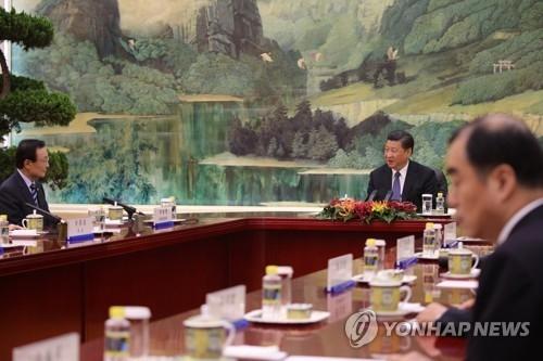中国国家主席习近平在人民大会堂与韩国特使李海瓒(左)交谈。(韩联社)