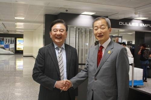 访美特使洪锡炫(左)20日在美国华盛顿杜勒斯机场与驻美大使安豪荣握手。(韩联社)