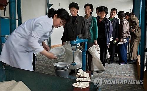 资料图片:朝鲜居民排队领取配给粮食。(韩联社)