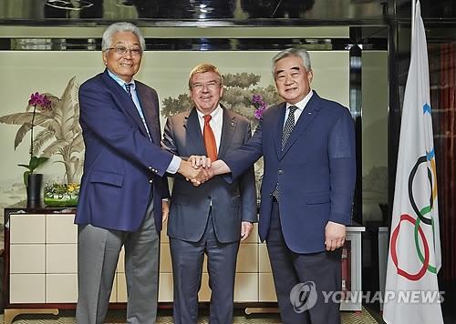 2014年8月21日,在中国南京,WTF秘书长赵正源(右)和ITF秘书长张雄(左)在IOC委员长托马斯·巴赫的见证下签署跆拳道发展意向书后握手合影。(韩联社)