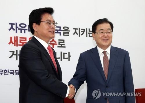 5月22日下午,在国会,青瓦台国家安保室长郑义溶(右)与自由韩国党党鞭郑宇泽握手。(韩联社)