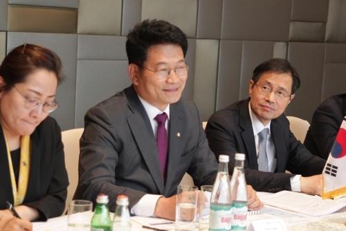 韩国总统特使宋永吉(中)与俄罗斯远东发展部官员交谈。(韩联社)
